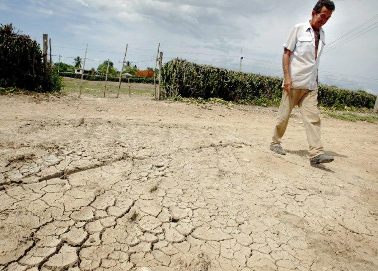 Rafael Aguilera walks around his dried-out farm in Holguin, some 435 miles east of Havana, Cuba.