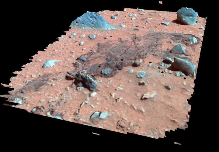 """An enhanced-color, 3-D reconstruction of the area around the Spirit rover landing site shows the """"Magic Carpet,"""" so named because of a crumpled portion of soil that appears to have been pulled awayin the lower left area of the image."""