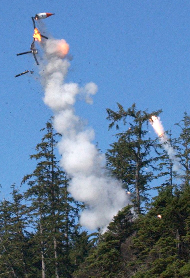 The Rubicon 1 rocket explodes Sunday shortly afterblastoff from an oceanside launch pad on Washington's Olympic Peninsula. The red and white rocket body is visible, as well as the long blackrocket engine casings.