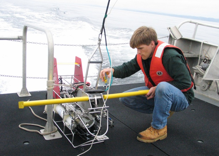 Crouched on the back of the research vessel Elakha, Oregon State University graduate student Anthony Kirincich on Tuesday attaches wings to a device called an Acrobat that controls the path of an array of instruments while they are towed behind the boat in the Pacific.