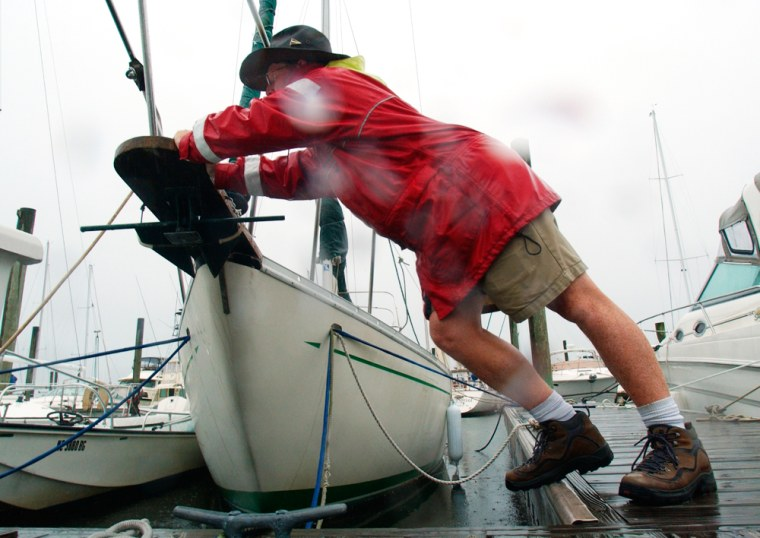 Dockmaster Bill Whaley pushes a boat as he adjusts lines in preparation for the arrival of Hurricane Charley in Wrightsville Beach, N.C., on Saturday.