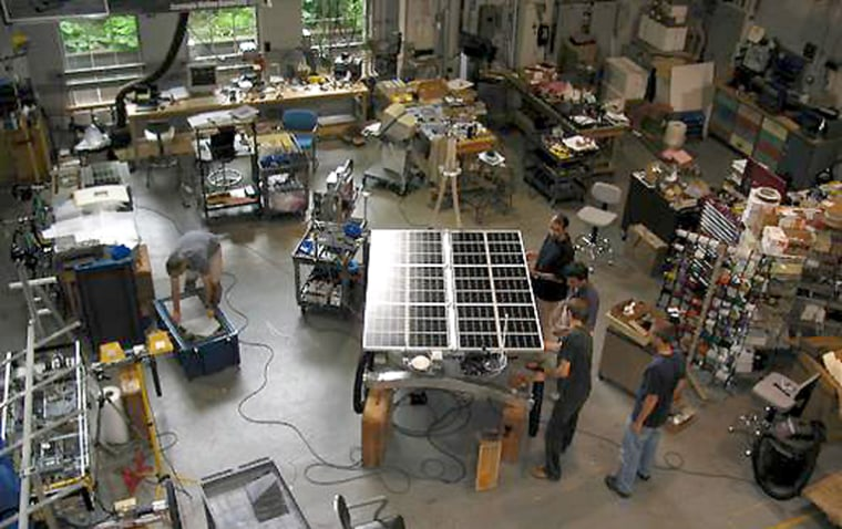 Researchers work on the solar-powered Zoë rover in the middle of a shop floor at Carnegie Mellon University.