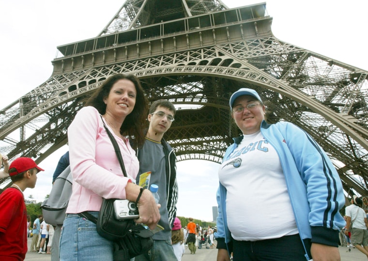 American tourists Nicole Nichols, left, from Florida; Alexin Hadji, center, and Georgina Nicolau, both from New England, stand Wednesday under the Eiffel Tower in Paris.