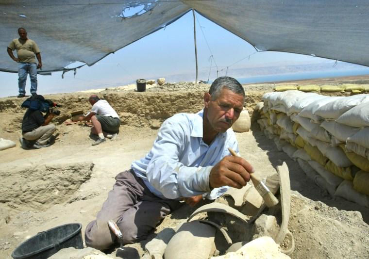 Yusuf Omaria uses a brush on Tuesday to remove dirt from a piece of an ancient pottery vessel in Qumran, an excavation site next to the Dead Sea. The project has sparked a debate over the ancient settlement that housed the Dead Sea Scrolls.