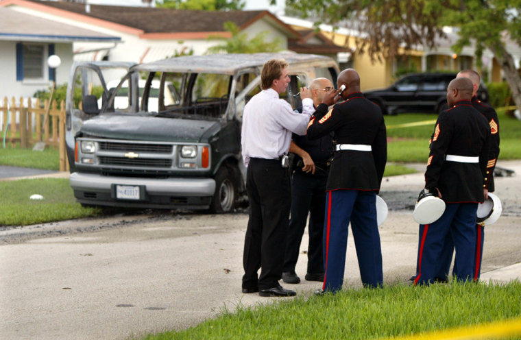 Police and Marines talked Wednesday near the Hollywood, Fla., home where Carlos Arredondo set himself on fire inside the Marine van in the background.