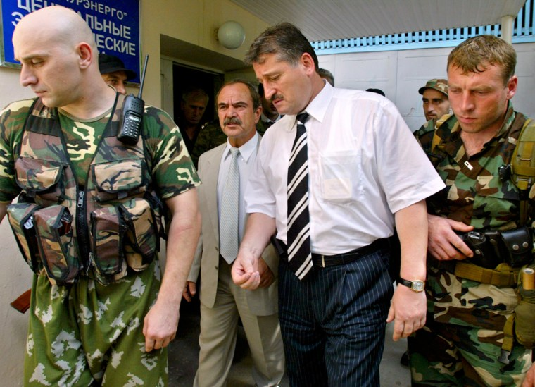 Surrounded by his bodyguards, Kremlin-favored candidate Alu Alkhanov leaves the central election commission in Grozny on Monday.