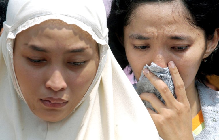 Relatives mourn Rina Dewi Puspita following her burial, on Friday, a day after she was killed in a bomb explosion outside the Australian Embassy in Jakarta, Indonesia.