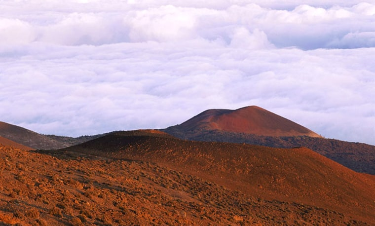 The summit of Mauna Loa, the highest volcano in the world, rises from the Hawaiian landscape.
