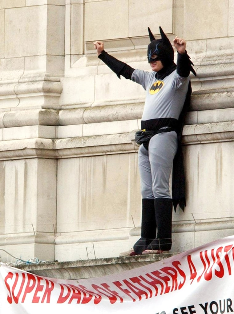 Protester Jason Hatch, dressed as Batman, stands on a ledge at London's Buckingham Palace, on Monday, near the balcony where the royal family appears on ceremonial occasions.