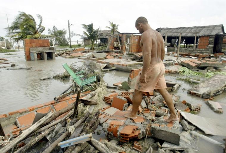 Man walking over debris of destroyed house after Hurricane Ivan brushes Cuba