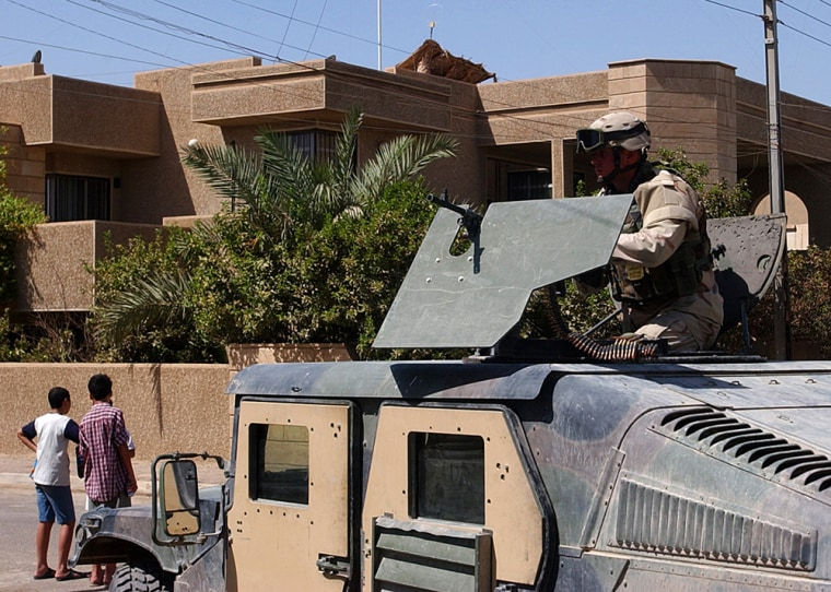 A U.S. soldier stands guard outside the house from which gunmen abducted the two Americans and a Briton.