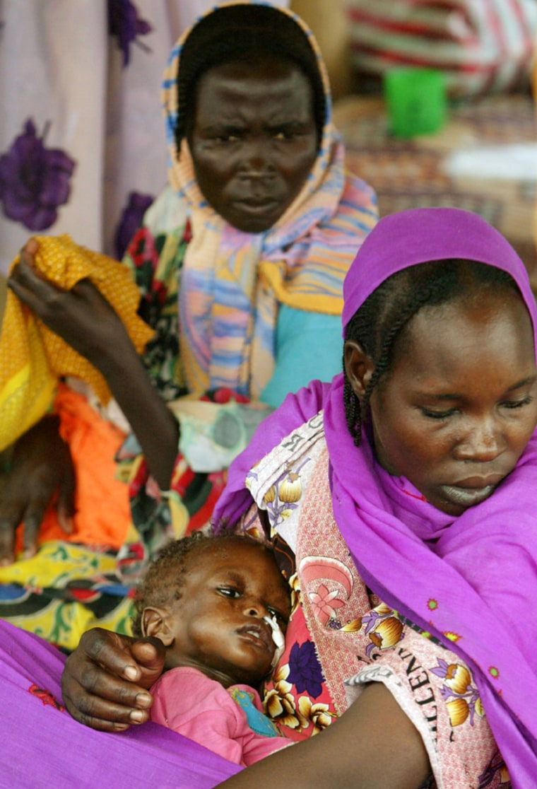 Displaced Sudanese women hold their malnurished children at feeding center run by Medecins Sans Frontieres within Kalma camp