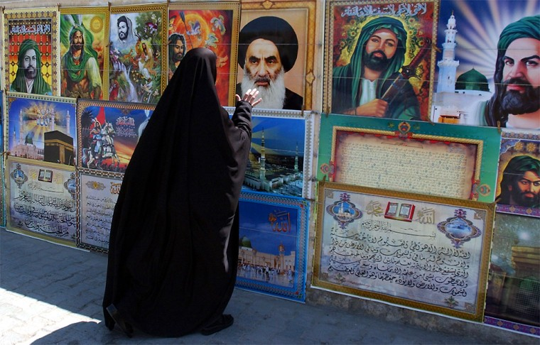 A woman reaches out to a picture of Grand Ayatollah Ali Husseini al-Sistani, posted alongside other Shiite religious figures in Baghdad, Iraq. Al-Sistani has been influential in pushing for early elections which would most benefit the county's large, majority-led political parties.