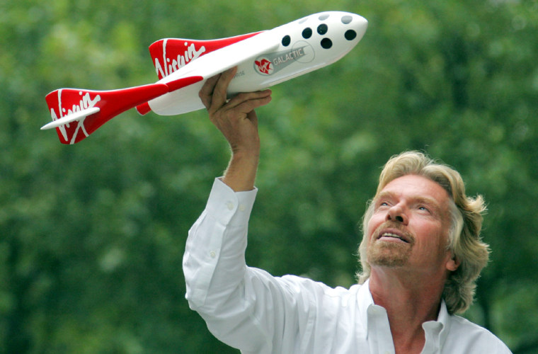 Sir Richard Branson holds model of a spacecraft at a news conference in central London