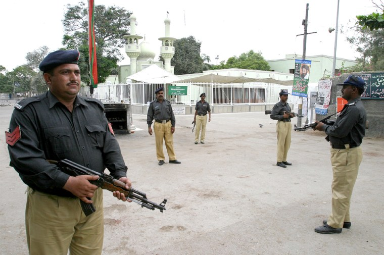 Pakistani policemen stand guard outside a mosque in Karachi
