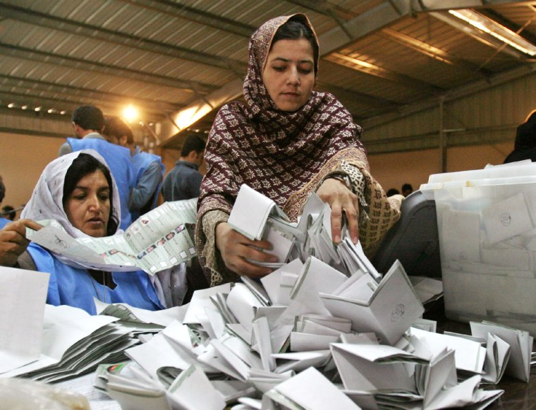 Afghan workers sort ballot papers at a counting center in Kabul