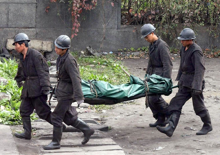 Rescuers carry a body of a miner from th
