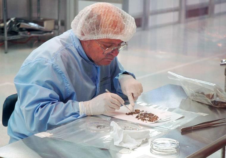 Don Burnett, principal investigator for NASA's Genesis mission, picks through shards of solar-wind samples from the broken spacecraft.