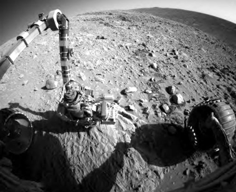 A picture from the Spirit rover's front hazard-avoidance camera shows the instrument-laden robotic arm poised over a geological target, with one of Spirit's wheels at lower right.