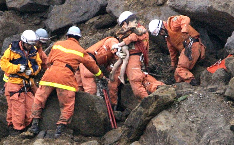 Rescuers remove Yuta Minagawa, 2, from a car buried in a landslide in Nagaoka on Wednesday.