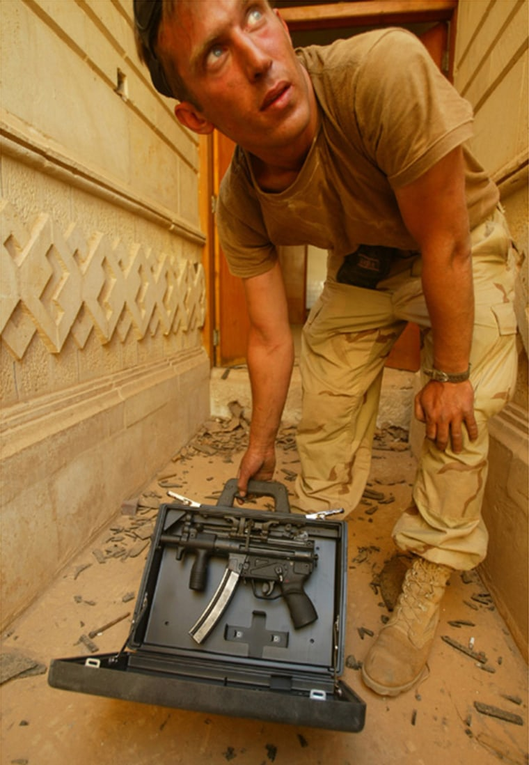 U.S. Army Sgt. Matt Novak, of Wisconsin, with one of the briefcase weapons recovered. LOS ANGELES TIMES PHOTO BY RICK LOOMIS