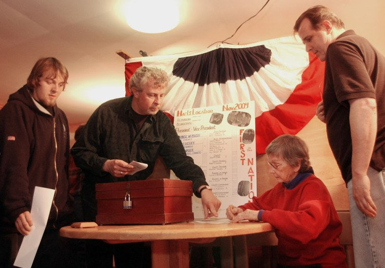 Marion Varney, seated, checks off voters' names as residents of Hart's Location, N.H., cast the first Election Day votes early Tuesday.