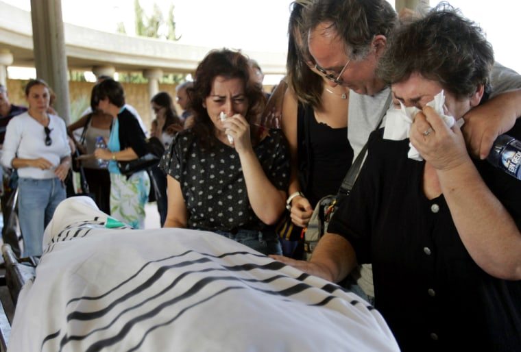 Buena Levi, right, is comforted by relatives as she touches the body of her husband, Shmuel, 65, during his funeral at Yarkon cemetery on the outskirts of Tel Aviv, Israel, on Tuesday, after he was killed in a suicide bombing on Monday.