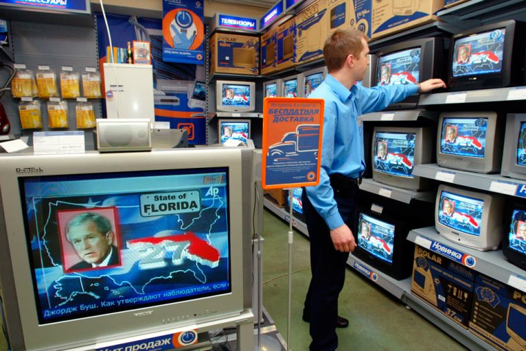 A shop assistant watches TV news about the U.S. elections in a Moscow shop on Wednesday.