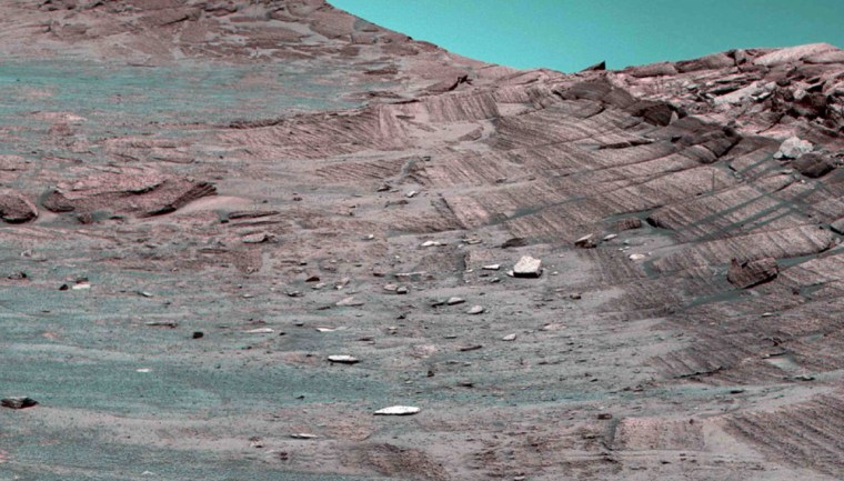 """Thisimage from the Opportunity rover shows Burns Cliff inside Endurance Crater. The cliff rises to the right, but this view is off-kilter because the rover is on the incline. Opportunity will advance to the squarish white rocknear the center of this image,then turn around and head out of the crater. The colors have been """"stretched"""" to emphasize subtle differences in the rocks. Thus, the sky is actually not as blue as it appears here."""