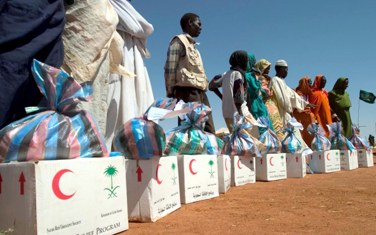 Displaced Sudanese people standnext toboxes of aid from the Saudi Relief Agency on Tuesday in el-Sereif refugee camp, in Sudan's western Darfur region.