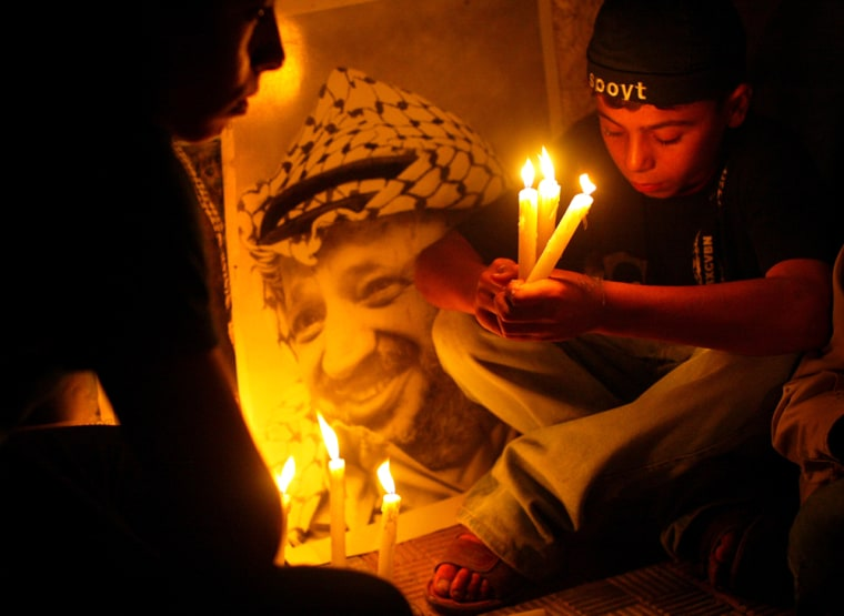Palestinianshold candles next to portraits ofYasser Arafat outside his former headquarters in Gaza City on Tuesday.