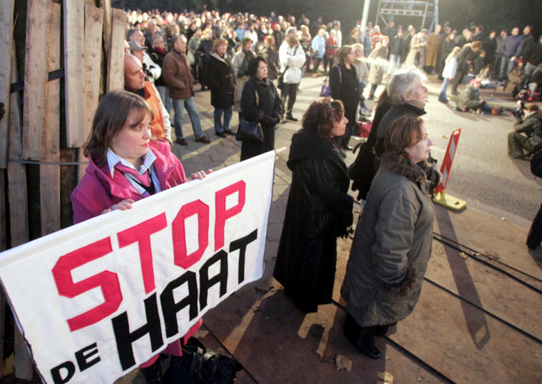 "A woman carries a banner reading ""Stop the hatred"" Tuesday while watching the funeral service for filmmaker Theo van Gogh in Amsterdam."