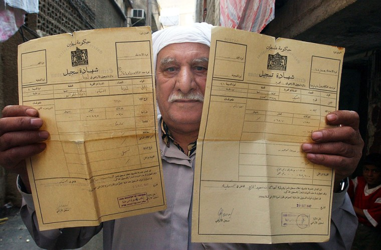Abu Ahmad al-Sukari, 70, a Palestinian refugee who lives in the al-Yarmouk camp on the outskirts of Damascus, Syria, holds up property deeds for lands in Israel.