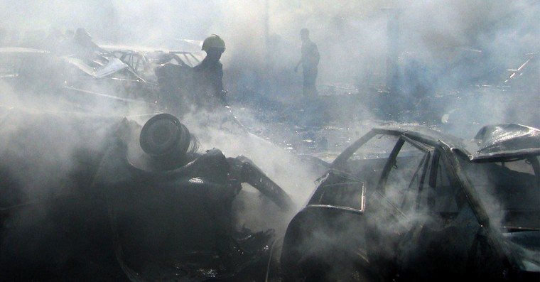 A firefighter hoses wreckage at the scene of acar bombing Thursday in downtown Baghdad.