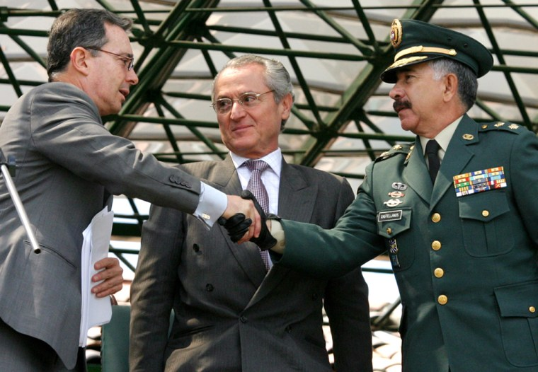 The new head of the Colombian army, Gen. Reinaldo Castellanos, right, shakes hands Thursday with Colombian President Alvaro Uribe during a military ceremony at a base in Bogota, Colombia. Defense Minister Jorge Alberto Uribe stands between them.