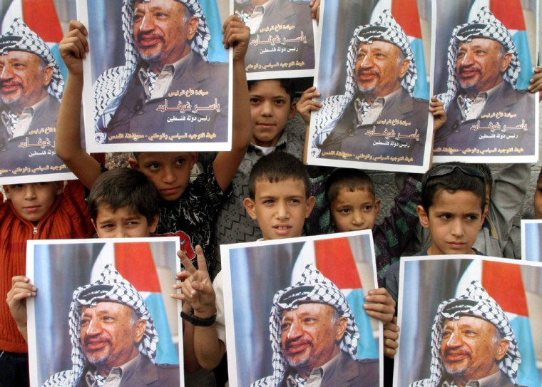 Palestinian children hold posters of Palestinian President Yasser Arafat during a rally following the announcement of his death, in east Jerusalem