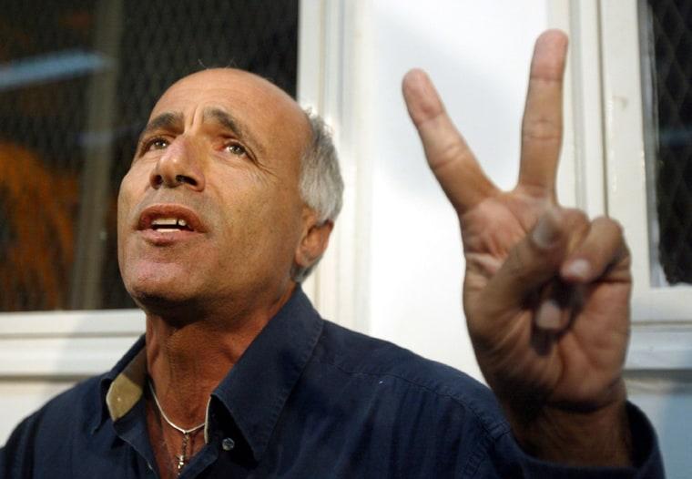 Mordechai Vanunu gestures as he speaks with journalists at a court in Petach Tikva
