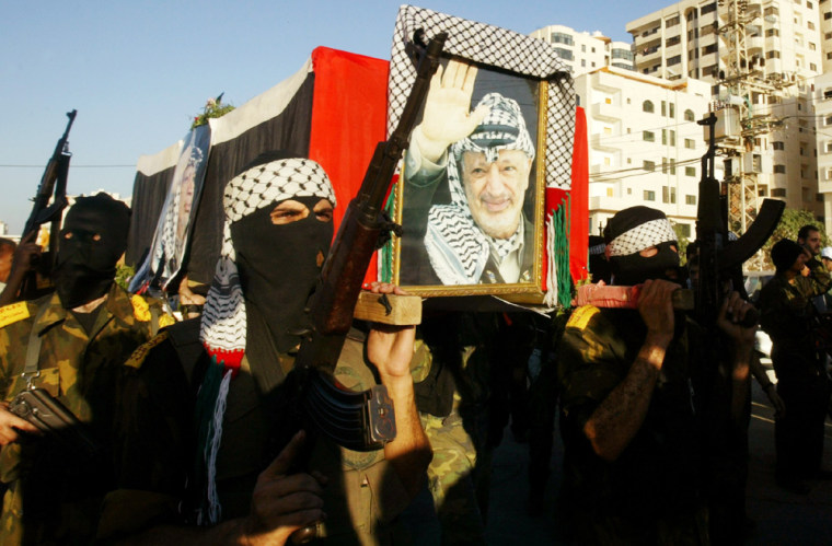 Masked Palestinian militants carry a coffin covered with the Palestinian flag and posters of president Yasser Arafat during a mock funeral in Gaza