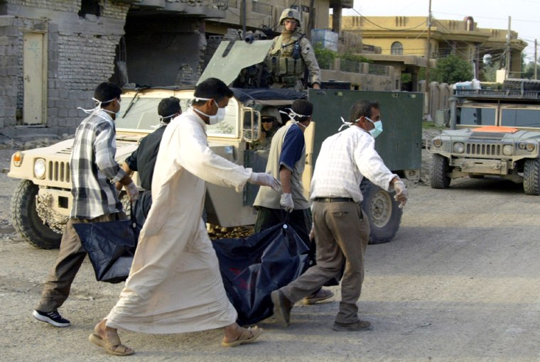Iraqis carry a body in a bag as they wal