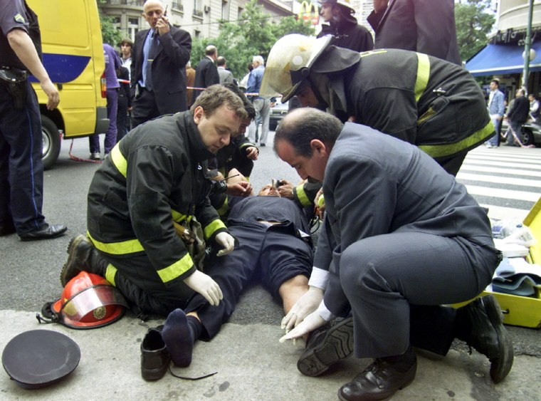 Security guard gets aid after explosion struck a Citibank branch in Buenos Aires