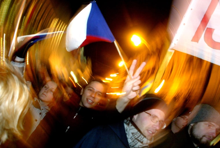 A marcher flashes a V-sign and waves a Czech flagat a Wednesday march commemorating the 15th anniversary of the 1989 Velvet Revolution in Prague, Czech Republic.