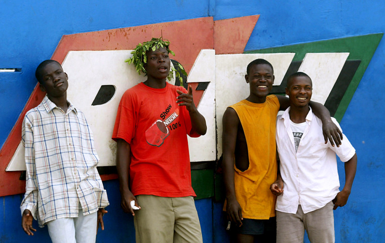Anti-French protesters stand Thursday at the main gate to RTI, Ivorian Radio Television in Abidjan, Ivory Coast.