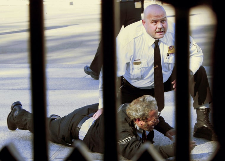 A uniformed member of the U.S. Secret Service guard is seen with a man on the ground who set himself on fire outside the White House fence in November.