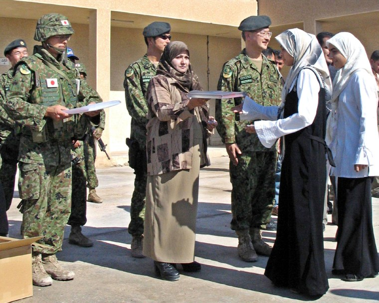 Japanese soldiers distribute school books to students in  the southern city of Samawa