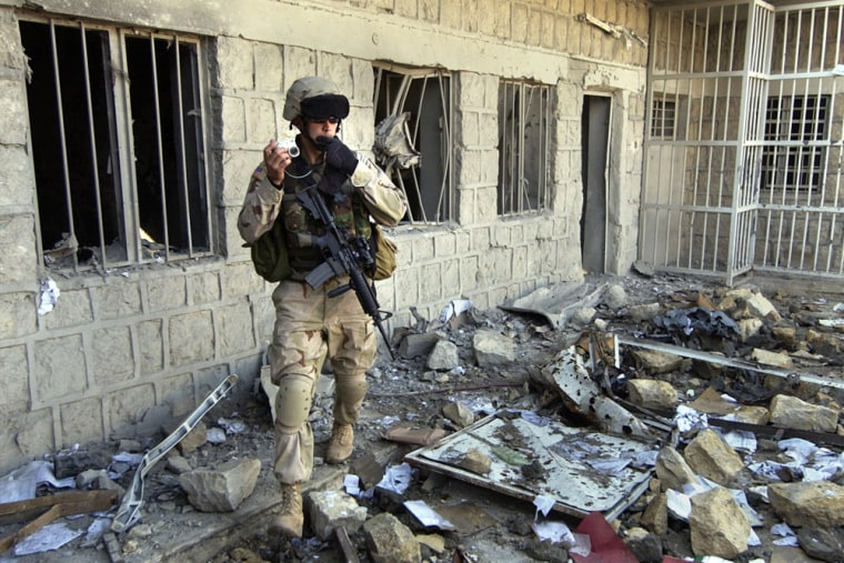 A U.S. Army soldier on Sundayphotographs the destruction inan Iraqi police station damaged in a recent insurgent attack in Mosul.