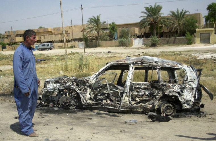 """A man walkspast a destroyed carin Latifiyah, located inIraq's infamous """"Triangle of Death,"""" on Sept. 5."""