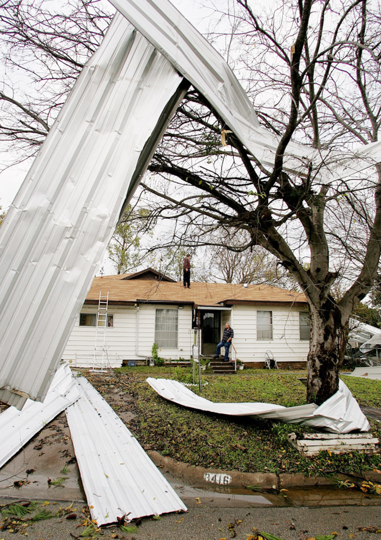 Sheets of corrugated steel are shown twisted in a tree and strewn around Johnny McCoy's front yard in Grand Prairie, Texas, after severe weather ravaged the area Tuesday.