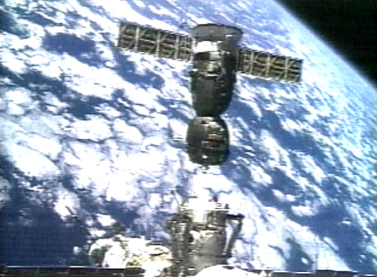 In an image take from video, the Soyuz crew capsule separates from the international space station to move to another docking port, against the background of a cloud-mottled Earth.