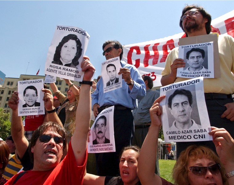 Former political prisoners and their relatives hold pictures of alleged torturers during a Monday demonstration in front of the presidential palace of La Moneda in Santiago, Chile.