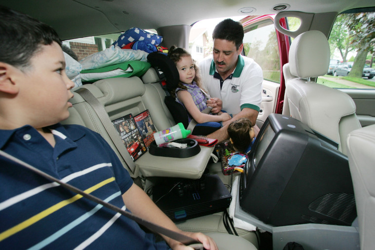 Kyle Faldoski, 12, left, watches as his father Mark buckles in sister Kensie, four, in Uniondale, N.Y, May 22, 2004, as the family prepares to travel from Long Island to Ohio.